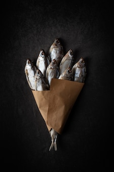 A bunch of dried fish on a black background with craft paper