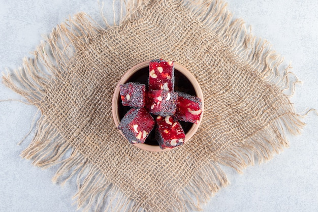 Bunch of dried red fruit pulps with nuts in ceramic bowl.