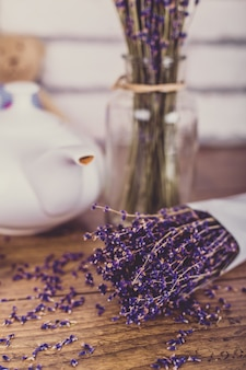 Bunch of dry cut lavender and teapot on wooden table. white bricks .