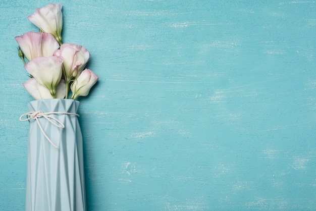 Bunch of eustoma flowers in vase on blue textured backdrop