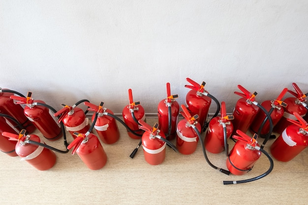 Bunch of expired fire extinguishers on the floor next to the wall.