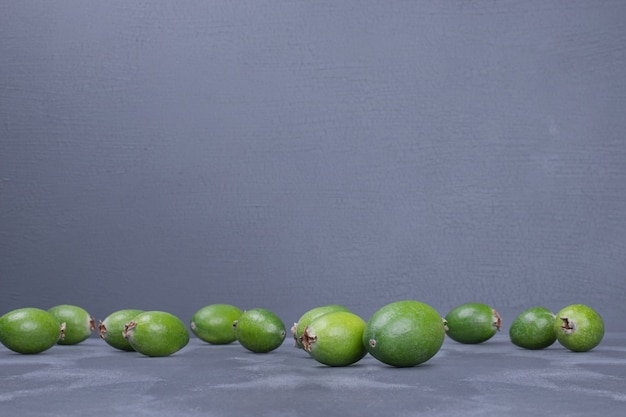 Bunch of feijoas on blue table.