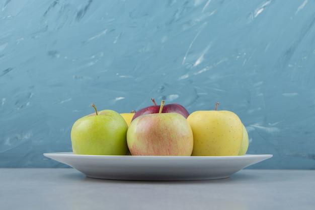 Mazzo di mele fresche sul piatto bianco.