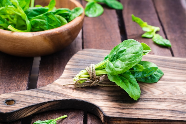 A bunch of fresh baby spinach leaves on a cutting board and spinach leaves in a bowl on a wooden table