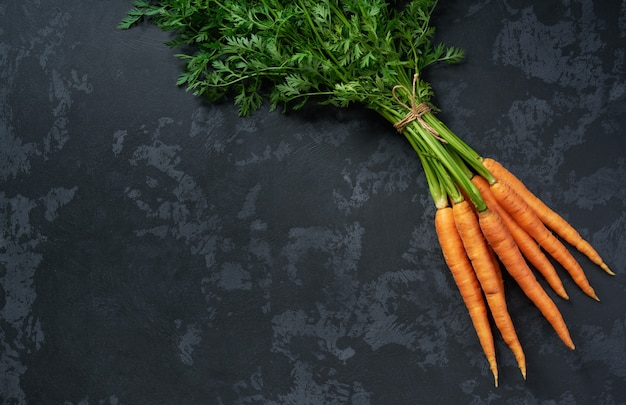 Bunch of fresh carrots on black background, top view.
