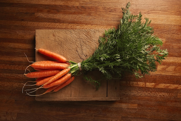 A bunch of fresh carrots on a weathered old cutting board with deep cuts on a beautiful wooden brown table, top view