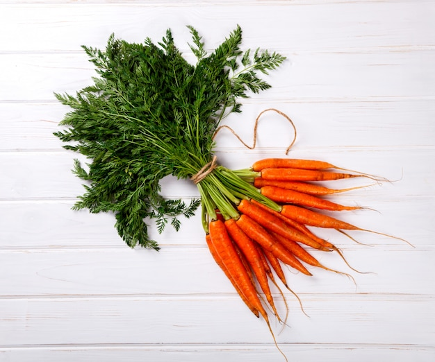 Bunch of fresh carrots with green leaves on a white background