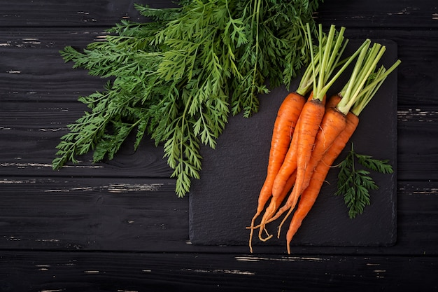 Bunch of fresh carrots with green leaves on wooden background.flat lay. top view