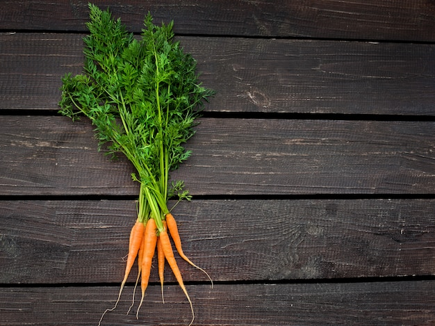 Bunch of fresh carrots with green leaves over wooden background