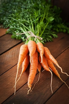Bunch of fresh carrots with green leaves over wooden table