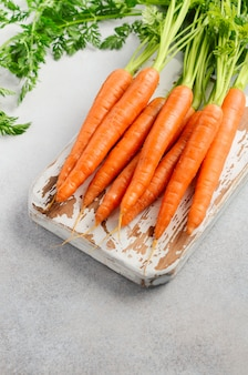 Bunch of fresh carrots on wooden cutting board.