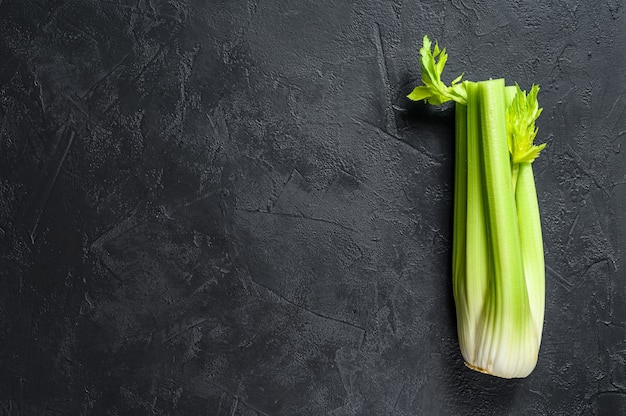 Bunch of fresh celery stalk with leaves. black background. top view. copyspace