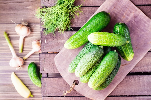 A bunch of fresh cucumbers and garlic on a wooden table