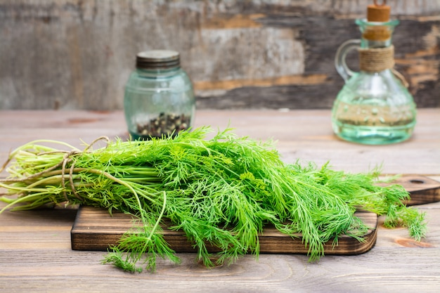 A bunch of fresh dill on a cutting board on a wooden table