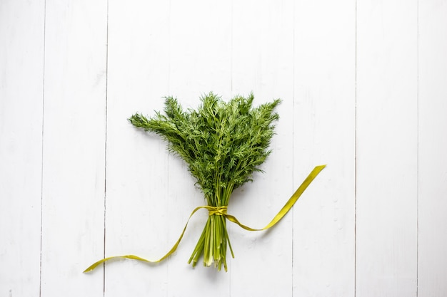 Bunch of fresh dill with ribbon on white wooden rustic background