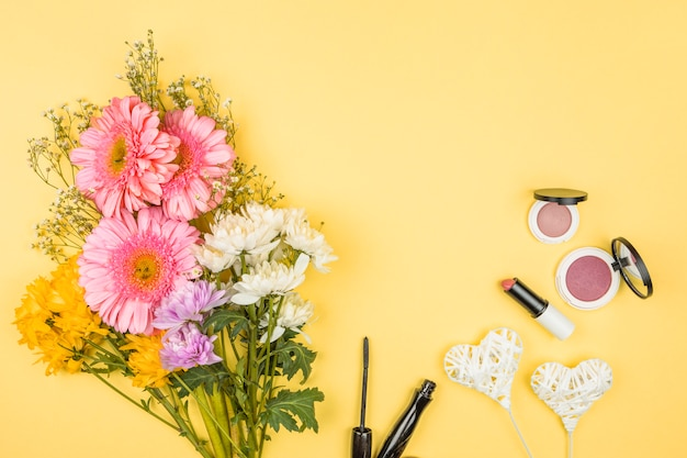 Bunch of fresh flowers near ornamental hearts on wands and lipsticks with powders