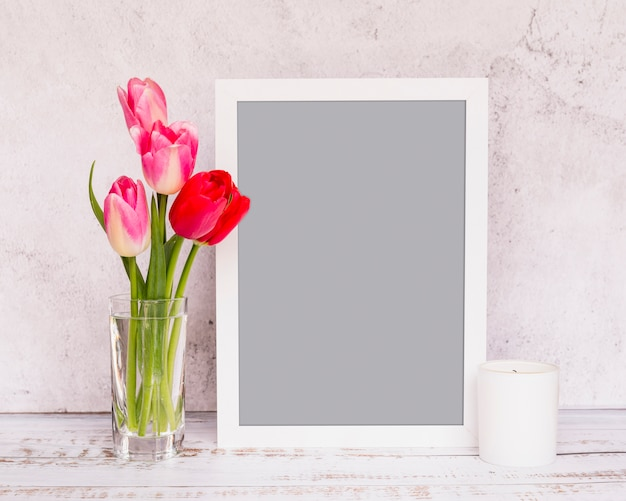 Bunch of fresh flowers on stems in vase near frame and candle