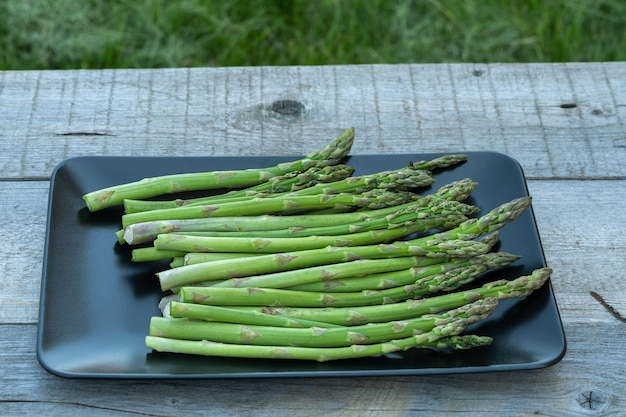 Bunch of fresh green asparagus spears in a black plate on a rustic wooden table summer outdoor.