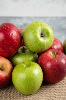 Bunch of fresh green and red apples placed on burlap.