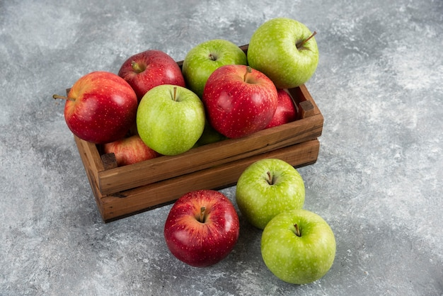 Bunch of fresh green and red apples placed in wooden box.