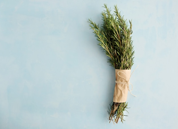 Bunch of fresh green twigs of rosemary wrapped in paper and tied with a rope lies on a blue background.