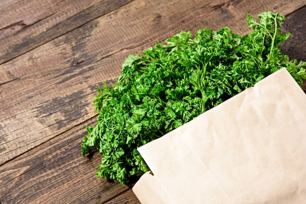 Bunch of fresh greens, parsley in an eco-friendly paper bag on a wooden background with close-up copy space