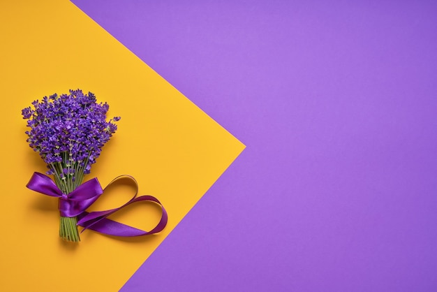 Bunch of fresh lavender on yellow-purple background. violet flowers. greeting floral card with place