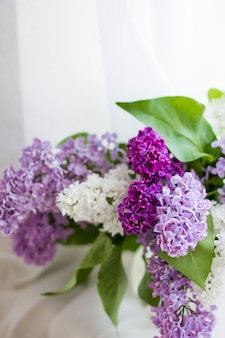 Bunch of fresh lilac flowers in glass vase close up