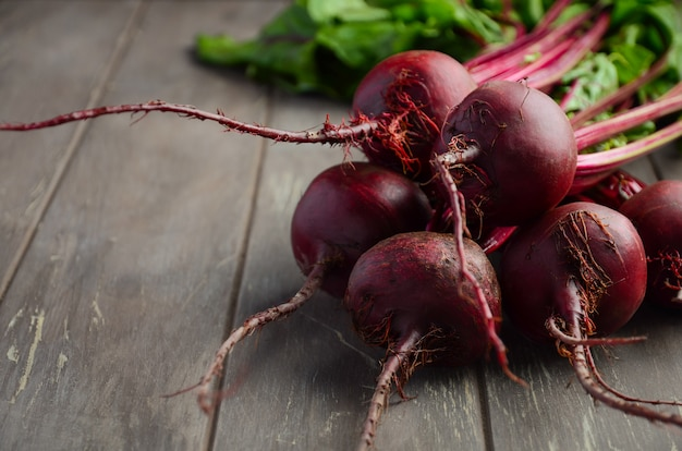 Bunch of fresh organic beets on rustic wooden table.