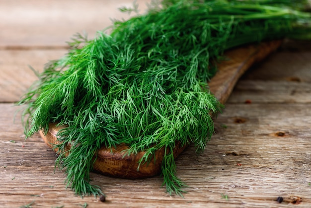 Bunch of fresh organic dill on wooden with copyspace, rustic and vintage style, selective focus