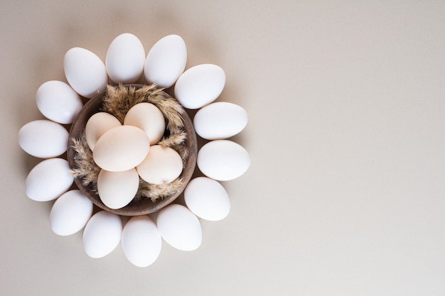 Bunch of fresh organic raw eggs placed on beige table.