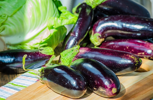 Bunch of fresh purple eggplants on a chalkboard
