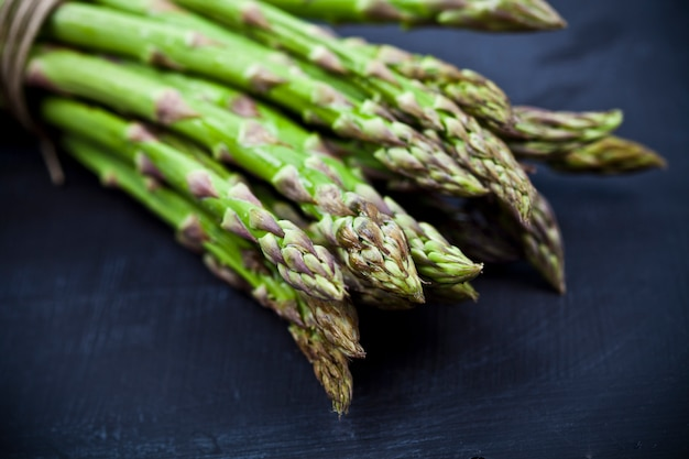 Bunch of fresh raw garden asparagus closeup on black board background.