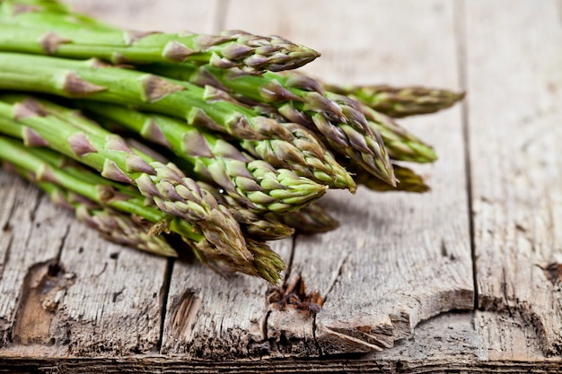 Bunch of fresh raw garden asparagus closeup on rustic wooden table background.