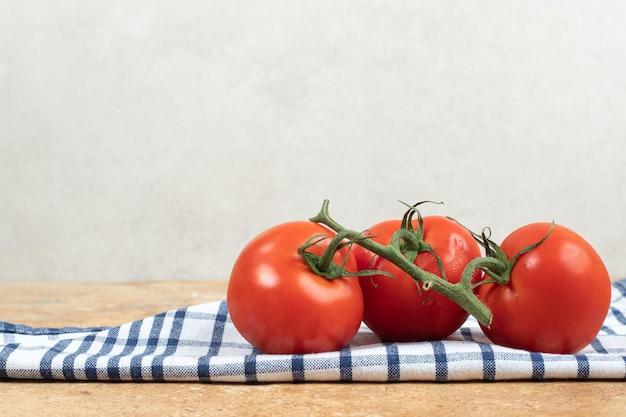 Mazzo di pomodori freschi e rossi con steli verdi sulla tovaglia