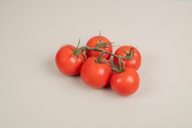 Mazzo di pomodori freschi e rossi con steli verdi sul tavolo bianco.