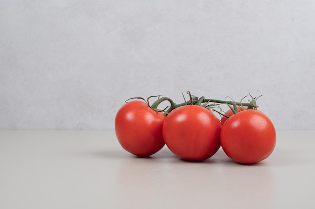 Bunch of fresh, red tomatoes with green stems on white table.