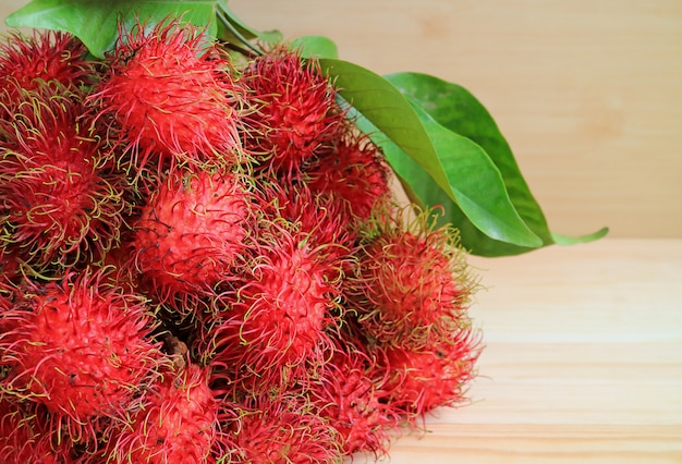 Bunch of fresh ripe rambutan fruits with green leaves on the wooden table