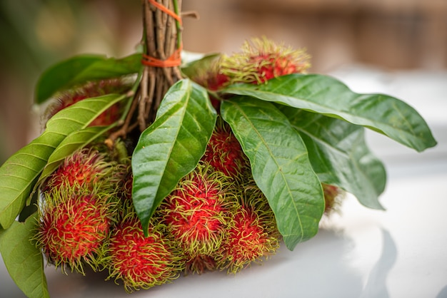 Bunch of fresh ripe rambutan fruits with green leaves.