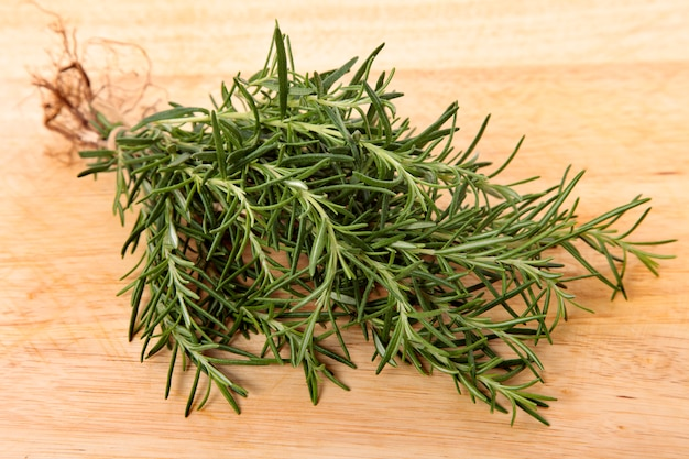 Bunch of fresh rosemary on wooden board