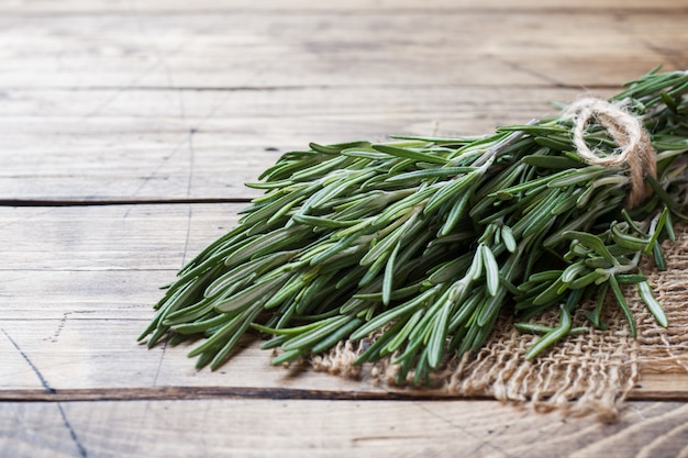 Bunch of fresh rosemary on wooden surface. copy space.
