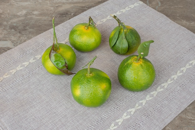 Bunch of fresh tangerines on gray tablecloth.