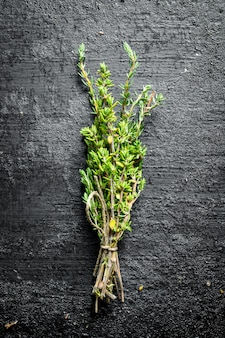 Bunch of fresh thyme. on black rustic surface