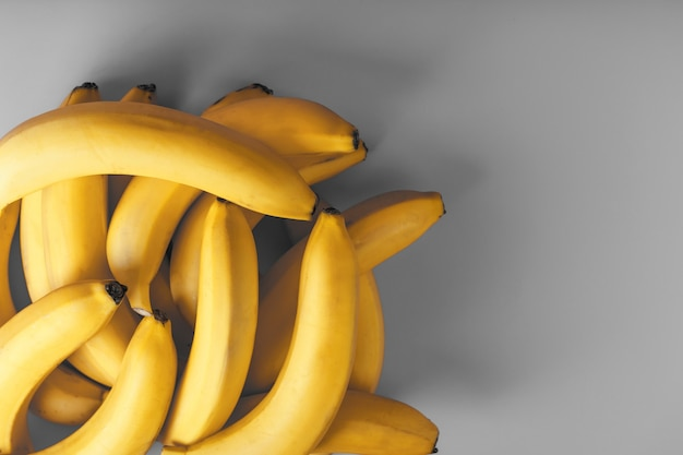 A bunch of fresh yellow bananas on a gray background in the fashionable colors of 2021.