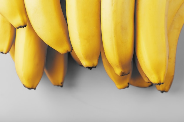 A bunch of fresh yellow bananas on a gray surface