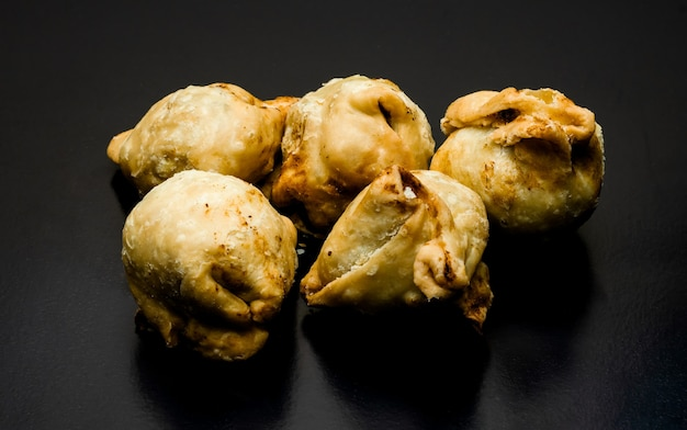 A bunch of fried samosas on a textured dark background