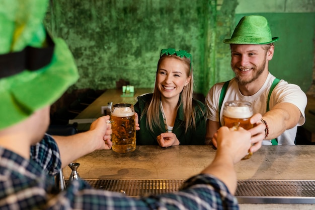 Bunch of friends celebrating st. patrick's day with drinks at the bar