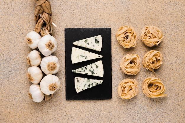 Bunch of garlic bulbs; cheese slices on tray and raw pasta arranged in row over marble wallpaper