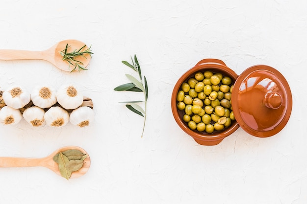 Bunch of garlic bulbs with herbs and fresh green olives