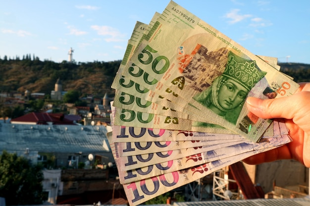 Bunch of the georgian 50 banknotes with blurry tbilisi city view in background